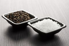 Salt and pepper. Into black bowls on wooden table stock photos