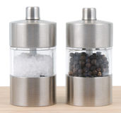 Salt and Pepper shaker. Salt and Pepper mill on cutting board with salt Royalty Free Stock Image