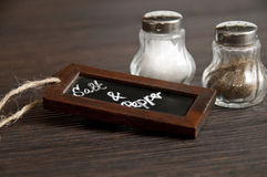 Salt and pepper shaker with chalkboard on wood Stock Photography