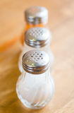 Salt and pepper in shaker glass bottle on wood table Stock Photography