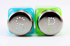 Salt & Pepper shakers. Salt &pepper shakers made from glass on withe Stock Photo