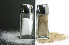 Salt and Pepper Shakers. Salt shaker on black background and pepper shaker on white background Royalty Free Stock Image