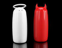 Salt and pepper shakers as angel and devil. On a black background Royalty Free Stock Images