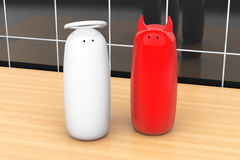 Salt and pepper shakers as angel and devil. On a kitchen table Royalty Free Stock Images