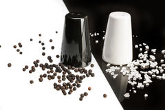 Salt and pepper shakers, black pepper and salt crystals Royalty Free Stock Image