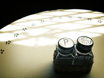 Salt & pepper shakers, cafe table in sunlight Royalty Free Stock Photos