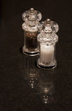 Salt and pepper shakers on a dark background. Salt and pepper grinders on a dark reflective kitchen surface. Photo has short depth of field, with focus on the Royalty Free Stock Photo