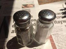 Salt and Pepper. Shakers sitting on newspaper Royalty Free Stock Images