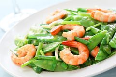 Salt and pepper shrimp with snow peas Stock Photos