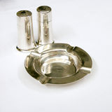 Salt and Pepper. A silver crudité set of a salt and pepper shaker along with a matching ashtray on a white tablecloth Royalty Free Stock Photography