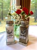 Salt and Pepper in Style. Close-Up of a white-clothed, corner table. On either side is a window view of tall, blurred trees in shades of green. Center: Tall stock photography