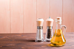 Salt and pepper and sunflower oil on brown desk side view Stock Image