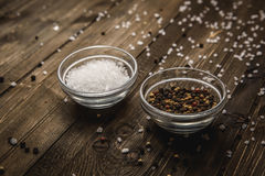 Salt and pepper on a wooden Board. Void wooden background of cutting board with wooden texture and scattered spices on it. Top view on void wooden background Royalty Free Stock Photography