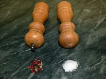 Salt and pepper. Wooden pepper mill and salt shaker on the kitchen countertop. salt and pepper recess Royalty Free Stock Images