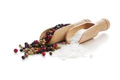 Salt and pepper on wooden shovels. Rough salt and mixed peppercorns on wooden shovels. high angle view stock image