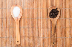Salt and pepper on wooden spoon. Brown background Royalty Free Stock Image