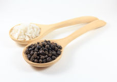 Salt and pepper in a wooden spoon.  on white background. Herbs Stock Photography