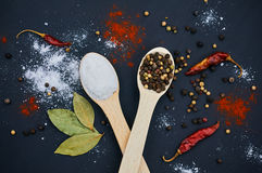 Salt and pepper on wooden spoons. With deco. Salt and pepper on wooden spoons. Decorate with bay leaves and chilli. Dark background. Close-up. Selective focus Royalty Free Stock Image