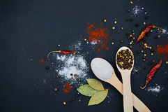 Salt and pepper on wooden spoons. Decorate with bay leaves and chilli. Dark background. Close-up. Selective focus Stock Photos