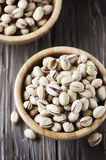 Salt pistachio nuts in the wooden bowl Royalty Free Stock Photography