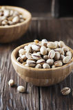 Salt pistachio nuts in the wooden bowl Stock Photo