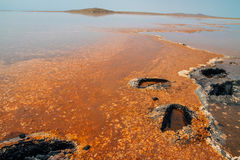 Salt pond with orange stains and clear blue sky Stock Photography