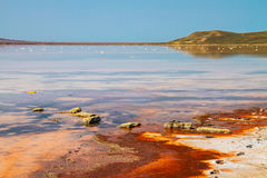 Salt pond with orange stains and clear blue sky Royalty Free Stock Photos
