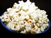 Salt popcorn i en blå bunke arkivfoton