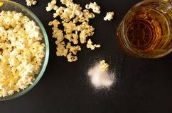 Salt popcorn och en råna av öl Royaltyfria Foton