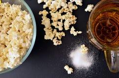 Salt popcorn och en råna av öl royaltyfri bild