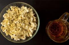 Salt popcorn och en råna av öl arkivbild