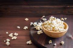 Salt popcorn på trätabellen royaltyfria bilder