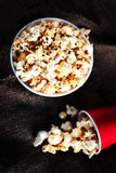 Salt popcorn in a red cardboard box on the wooden table, Cinema Stock Image