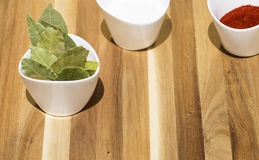 Salt, red pepper and Bay leaf on a wooden background. Stock Photography