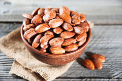 Salt roasted almond in wooden bowl on wooden table Stock Photo