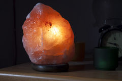 The salt rock lamp. A lamp made with an Himalayan salt rock turned on Stock Image