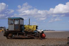 Salt rusted workhorse of a fishing tractor. Trusty old tractor used for dragging out the fishing boats, parked up and looking out to sea under a blue summer sky Stock Image