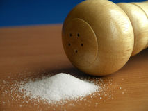 Salt and saltshaker. Saltshaker and spilled salt on the table Royalty Free Stock Images