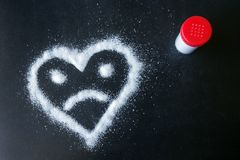 Salt scattered on black surface. Drawn heart with a sad face. Concept- diet, harm to health from excessive consumption of salt and sugar stock photography
