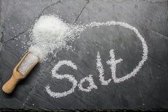 "Salt. Sea salt with the inscription ""salt"" on a dark background, selective focus Stock Image"