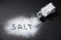 Salt shaker on black table. The word salt written into a pile of white salt and salt shaker on black table royalty free stock photos