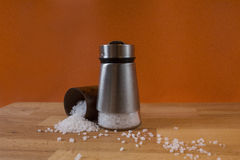Salt shaker. A salt shaker and some spilled salt near it Stock Photography
