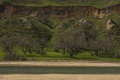 Salt sjö och gröna kullar och klippa royaltyfri bild