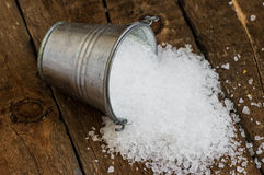 Salt spill out of the bucket tin on a wooden board Stock Photo