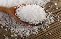 Salt in spoon on  wooden  background. Stock Image