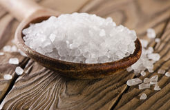 Salt in spoon on  wooden  table. Stock Photos