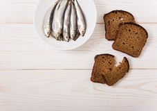 Salt sprat on the white plate with black bread.Minimalist style. White wooden background.Copy space Royalty Free Stock Photography