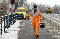 Salt Spreader in colorful work clothes, Jirnsum. By Snow and frost the bike path became dangerously slippery on a viaduct. A worker in orange workwear, which is Royalty Free Stock Image