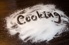 Salt sprinkled on the table with finger written word Royalty Free Stock Photo