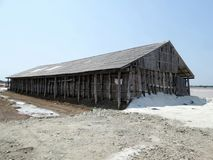 Salt storehouse for collect dried salt from saline. Wooden salt shed in Samutsongkram Province Thailand stock image